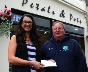 Courtney Moore from Petals & Pots presents Eugene Milligan with a sponsorship cheque