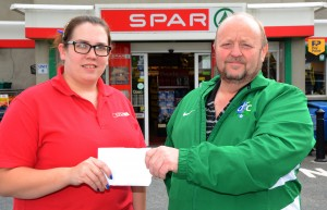 Eimear Mageean from Quinn's Spar, Saul Road, Downpatrick presents Thomas Leckey with a sponsorship cheque